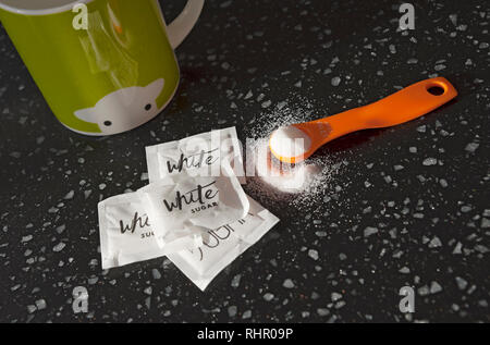 Close up of spoonful of white sugar and sugar sachets - Stock Image
