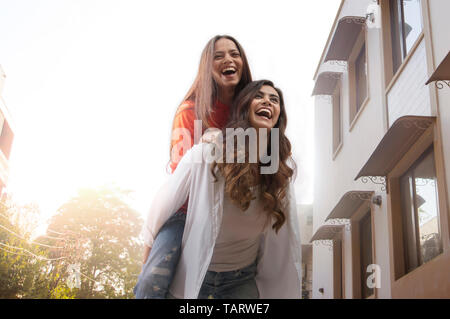 Woman carrying friend on her back walking outdoors in a street - Stock Image