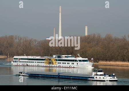 Cargo ship and cruise liner passing on the river Rhine, Cologne, Germany. - Stock Image