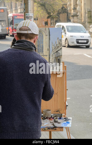 An artist painting Plein Air in High Street, Oxford, England, United Kingdom. - Stock Image