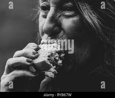 Woman eating sandwich in the open air - Stock Image