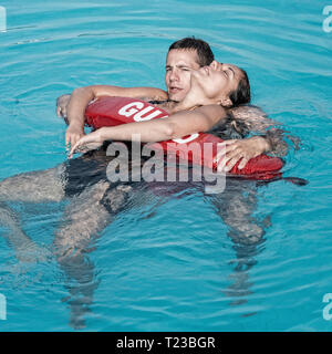 Lifeguard rescuing woman from water. - Stock Image