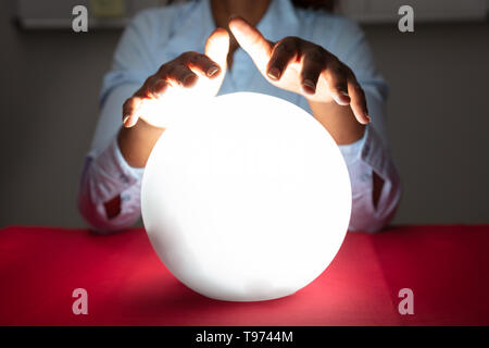 Close-up Of Fortuneteller's Hand Covering The Glowing Crystal Ball On Red Desk - Stock Image
