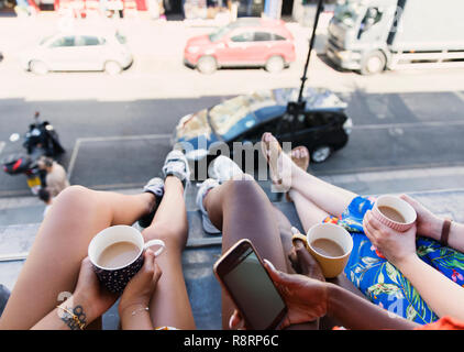 Women friends drinking coffee, dangling legs out urban apartment window - Stock Image
