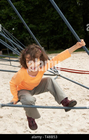 Little girl on a climbing frame at the playground - Stock Image
