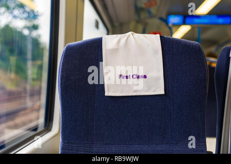 A train carriage window seat with First Class sign on it, UK - Stock Image
