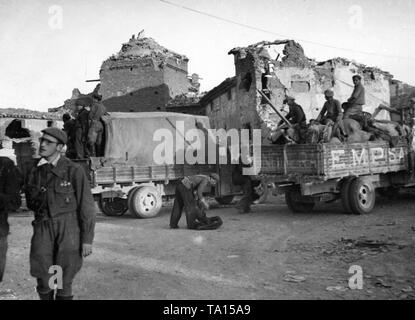 Photo of the city center of Belchite near Zaragoza, Aragon, Spain, in March, 1938. In the foreground, a Spanish national soldier. On the right behind there are trucks. In the background, houses shot to pieces. - Stock Image