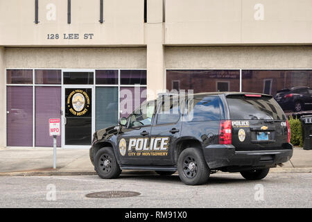 Black police or law enforcement SUV vehicle parked in front of a district or precinct headquarters building in Montgomery Alabama, USA. - Stock Image