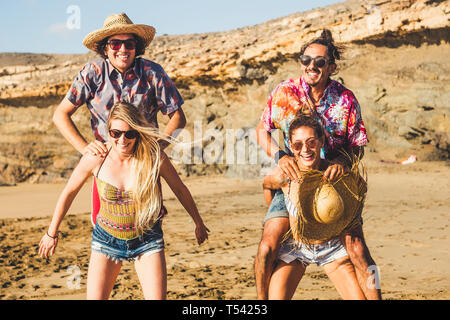Crazy group of people caucasian friends men and women playing together at the beach in vacation - men jump on the back of the woman that have to carry - Stock Image