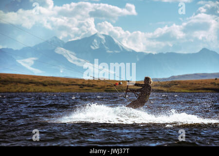 Woman kite surfing in mountain lake - Stock Image