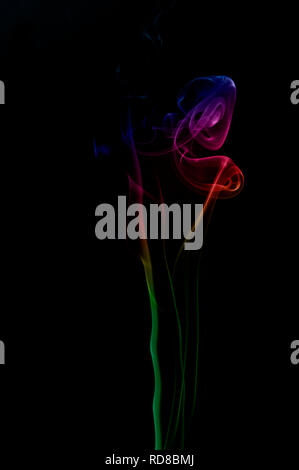 Coloured smoke against a black background - Stock Image