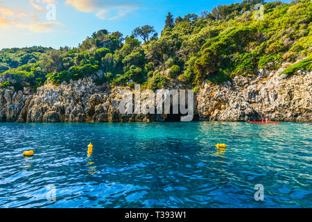 Two young women paddle board past the blue cave on the coast of the Greek island of Corfu on the Aegean Sea - Stock Image