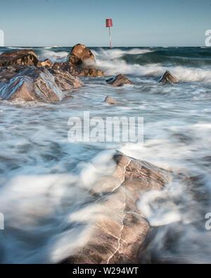 waves crashing over rocks on the coast - Stock Image