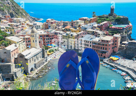 Blue flip flops on foreground with Vernazza, Cinque Terre - Italy, a popular tourist spot on the Ligurian Sea on background - digital composite - Stock Image