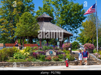 BLOWING ROCK, NC, USA,-23 AUG 2018: City Park, with a gazebo, flag pole, a couple walking. and woman using cell phone. - Stock Image