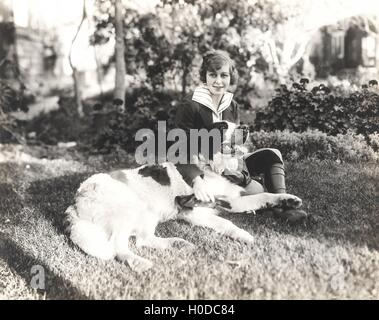 Woman sitting with her dog on grass - Stock Image