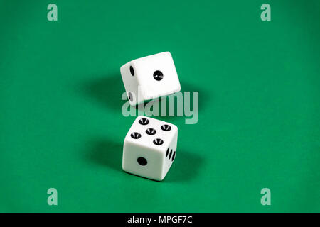 Craps is a dice game where players make wagers on the outcome of a pair of diced thrown down a table. - Stock Image