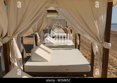 Luxury beach beds for two people with white roof and sides like a tent - Stock Image