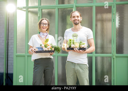 Portrait of a happy vegetarian couple holding boxe full of fresh raw vegetables outdoors on the green background - Stock Image