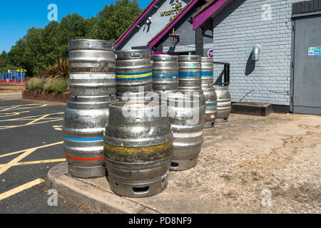 Metal beer barrels stacked outside a pub. - Stock Image