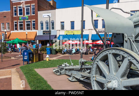 HICKORY, NC, USA-10/14/18: Downtown tables filled with lunch crowd near WWII German Howitzer cannon on display. - Stock Image