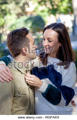 A young couple in love flirts in a public park - Stock Image