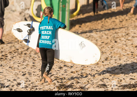 A young girl returning her surfboard after a surf lessoon with Fistral Beach Surf School in Newquay in Cornwall. - Stock Image