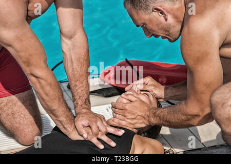 Lifeguards doing CPR after swimming pool accident. - Stock Image