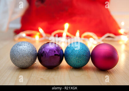 Four holiday ornaments on the floor with white lights and a red bag - Stock Image