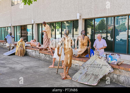 Religious figures depicting the human experience along the sidewalk in downtown Montgomery Alabama, USA. - Stock Image