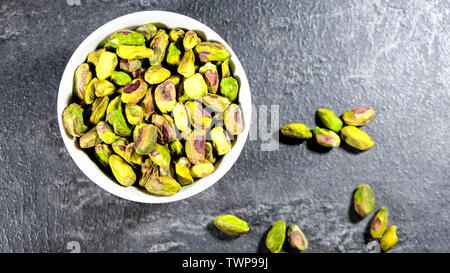 Bowl of Crunchy Healthy Pistachio Nuts or Kernels looking Down on a Table Top with No People - Stock Image