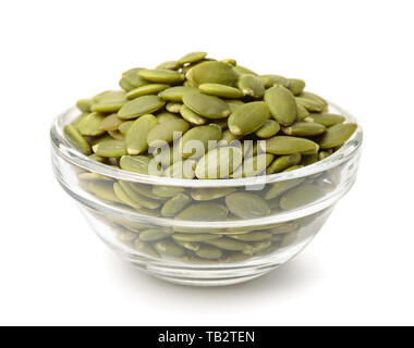 Glass bowl of pumpkin seeds isolated on white - Stock Image