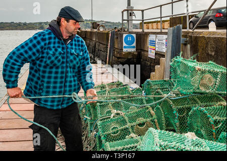 Schull, West Cork, Ireland. 11th Apr, 2019. A local fisherman prepares his crab pots before loading them onto his boat for a fishing trip later today. The weather is cold but dry with the sun starting to make an appearance. The day will remain mostly dry with top temperatures of 11 to 15°C. Credit: Andy Gibson/Alamy Live News - Stock Image