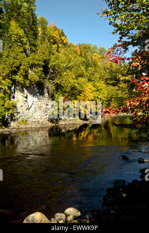 Trees in spectacular early autumn colours reflected in river parc Canyon Sainte Anne Quebec - Stock Image