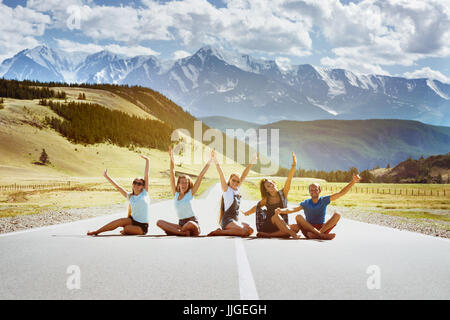 Group of five happy friends having fun sitting on the straight road on mountains background. Team or friendship - Stock Image