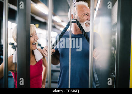 Vital mature couple exercising in the gym. - Stock Image