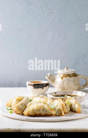Fried asian dumplings Gyozas potstickers in white ceramic plate served with bowl of soy onion sauce, teapot over white marble table. Grey wall at back - Stock Image
