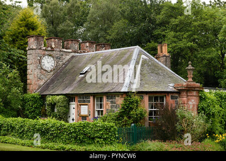 West Clock Lodge coach house in Sheriffmoor Plantation Forest at Eagle Lodge Scottish Borders Scotland UK with ivy and clock chimney - Stock Image