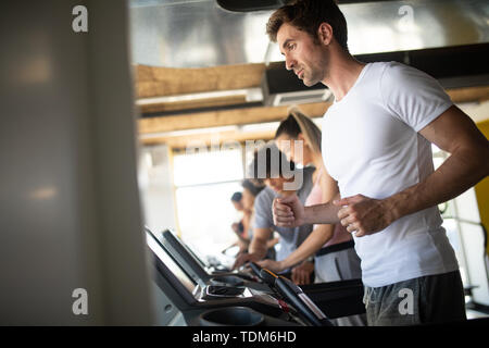 People running on treadmill in gym doing cardio workout - Stock Image