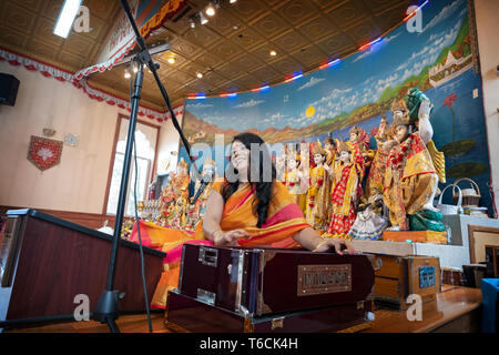 PANDITA. A female Hindu priestess sings a prayer while playing a harmonium at a temple in Jamaica, Queens, New York City. - Stock Image