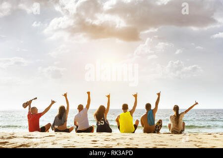 Group of happy friends having party at sunset sea beach. Space for text - Stock Image