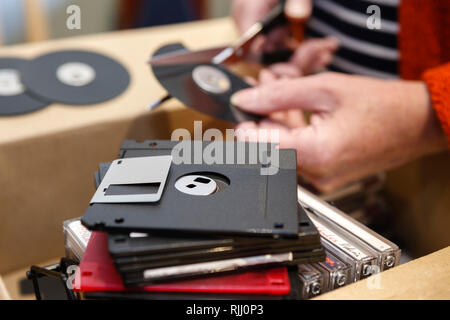 Cutting up old floppy disc with scissors to destroy information - Stock Image