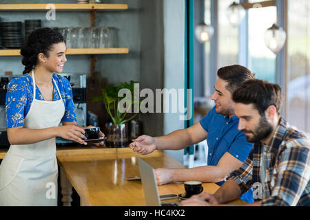 Waitress serving a cup of coffee to customer - Stock Image