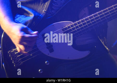 Bass guitarist on stage playing bass guitar - Stock Image