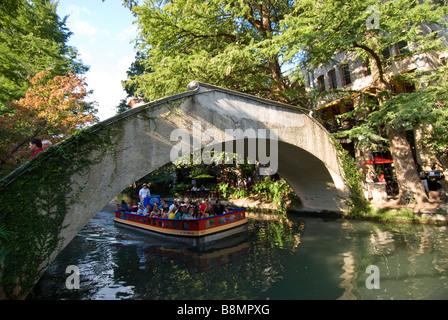 San Antonio Riverwalk boat goes under bridge on San Antonio River bright sunny day - Stock Image