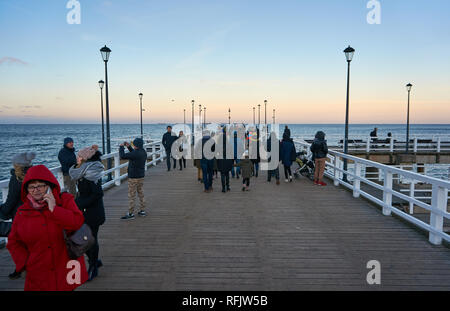 People strolling along a wooden pier stretching into the Baltic sea in Jelitkowo, Gdansk, Poland - Stock Image