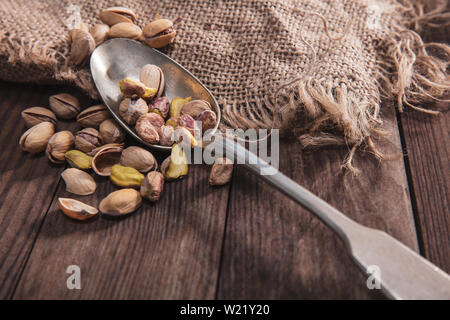 Pistachio nuts on an old spoon and composition from old wood and material - Stock Image