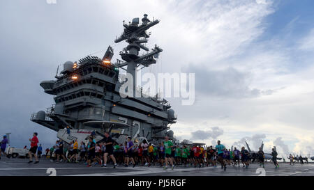 180826-N-JX484-022  ATLANTIC OCEAN (Aug. 26, 2018)  Sailors participate in the annual 'Run With The Chiefs' 5K on the flight deck of the Nimitz-class aircraft carrier USS Abraham Lincoln (CVN 72). Abraham Lincoln is currently underway conducting carrier qualifications. (U.S. Navy photo by Mass Communication Specialist 2nd Class Mark Andrew Hays/Released) - Stock Image