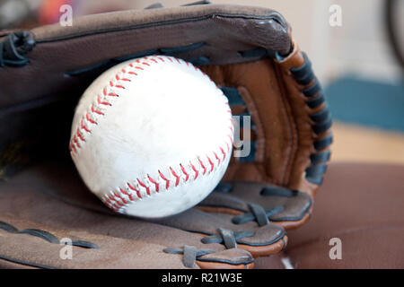 A softball and leather glove ready to play ball - Stock Image