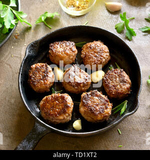 Close up of minced meat cutlets in frying pan over brown background. - Stock Image